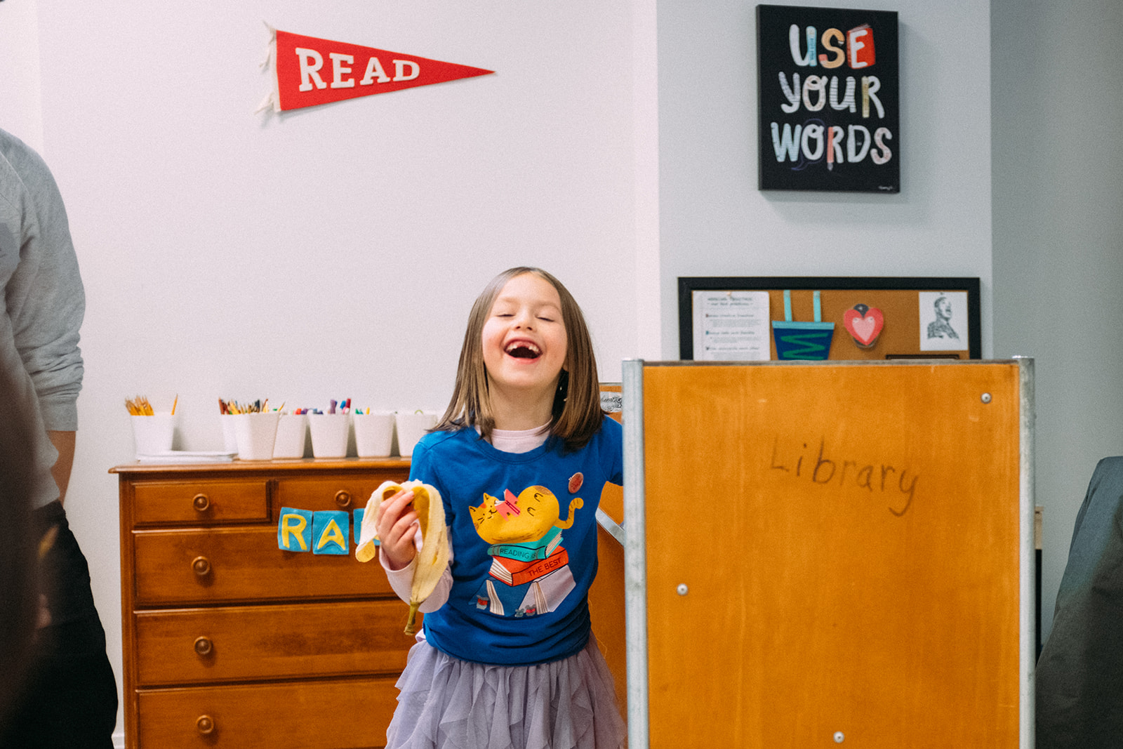 Child Laughing Near Bookshelves While Looking For Book - Read and Write Kalamazoo