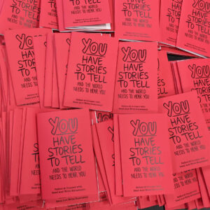 """a large pile of red booklets printed with the words """"YOU have stories to tell, and the world neesd to hear you"""""""